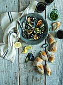 Gedämpfte Miesmuscheln serviert mit Brot und Rotwein