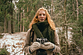 Portrait redhead woman with camera in snowy woods