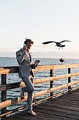 Barefoot businessman talking on smart phone on sunny pier, Los Angeles, California