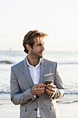 Businessman with smart phone on ocean beach