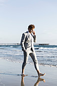 Barefoot businessman walking on sunny ocean beach, Los Angeles, California