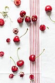 Fresh cherries and red strawflowers on a linen cloth