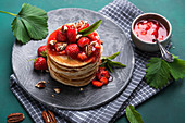 Vegan pancakes with strawberry compote, pecans and mint