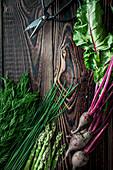 Dill, Schnittlauch, grüner Spargel und Rote-Bete auf Holzuntergrund