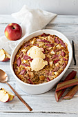 Baked oatmeal with apples and rhubarb, served with vanila ice cream