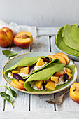 Green spinach crepes with cottage cheese and fresh peaches