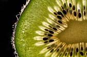 Closeup half of ripe kiwi with seeds and fluffy peel against black background