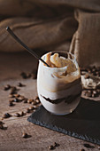 Glass of tasty cream coffee dessert with spoon served on black surface with coffee beans on wooden table