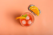 Top view of alcohol cocktail with ice cubes and sprig of mint in glass placed on pink background with orange slices