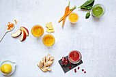 Colourful ginger shots made with apple, carrots, spinach and pomegranate seeds