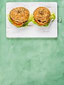 Veganer Burger: Dinkelbrötchen mit Soja-Gemüse-Patty, Salatblatt, Tomate und roten Zwiebeln