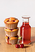 Freshly baked cherry muffins and bottle of stewed fruits drink