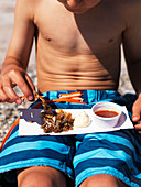 A boy in bathing shorts eating fried prawns and crab on the beach