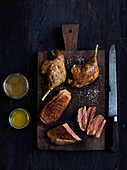 Roasted duck legs on a wooden chopping board