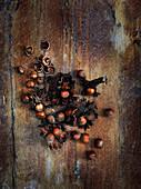 Whole Hazelnuts with One Cracked Open on Wood