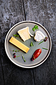 A cheese platter with herbs and chilli jam
