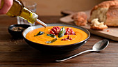 Drizzling pumpkin cream soup with olive oil