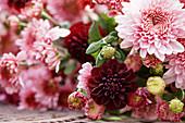 Herbststrauß aus Chrysanthemen und Dahlien liegend