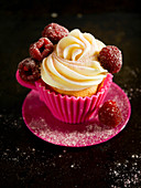A cupcake with buttercream and raspberries