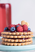 A layered biscuit tower with jam and berries