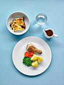 Hähnchen-Drumstick mit Kartoffeln und Gemüse dazu Dessert und Getränk