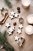 Cinnamon stars next to burning candles and fir tree branches