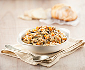 A bowl of quinoa risotto with mushrooms, carrots and vegetables.