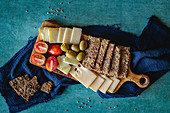 Cheese platter with olives, tomatoes and crispbread