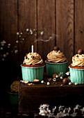 Cupcakes decorated with buttercream and chocolate malt balls, one with a smoking candle