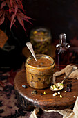 Glass jar of caramel sauce with dried fruit and nuts mixed in and alongside the jar