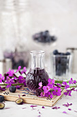 Small vintage bottle of violet liqueur surrounding by purple flowers