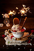 Vintage tea cup filled with raspberry ripple ice cream and topped with stroopwafel cookies and sparklers