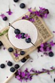 Overhead view of a cocktail with egg white foam that is decorated with blueberries and flowers