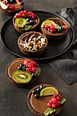 Dark and caramelized chocolate tarts with berries and nuts
