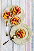 Fresh fruit tarts with caramel chocolate ganache, strawberries and apricots
