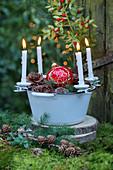 Adventskranz mit Kerzenhaltern an einer Emailleschüssel im Freien