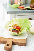 Lamb burger with tomato and cucumber on a lettuce leaf