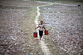 Boy carrying water, Myanmar