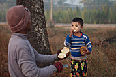 Boy eating coconut, Myanmar