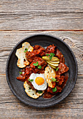 Fiakergulasch (Viennese-style goulash with beef topped with sausage, fried egg and gherkins) with cauliflower and a quail's egg