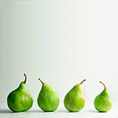Vier grüne Birnen in einer Reihe