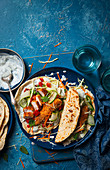 Wraps with panko coated chicken, minted yoghurt, tomato salsa, cucumber and cabbage and carrot slaw