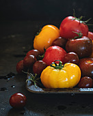Wet multicolored tomatoes on dark background