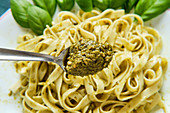 Spoon with pesto sauce and tasty Italian pasta