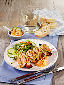 Grilled turkey roulade skewers with feta cheese, courgettes and tomatoes