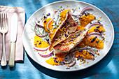 Gebratene Fischfilets auf Orangen-Zwiebel-Salat mit Fenchelgrün und Essblütenblätter