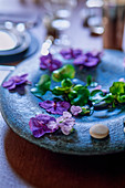 Purple flowers on a stone plate as table decoration