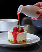A mini cheesecake with fruit sauce