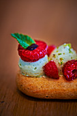 Eclair with pistachio cream and raspberries