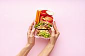 Frauenhände halten Lunchbox mit gesunden Snacks